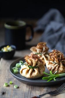 Crêpes sous forme de sachet farci d'oeufs et d'oignons. assiette de crêpes sur fond noir