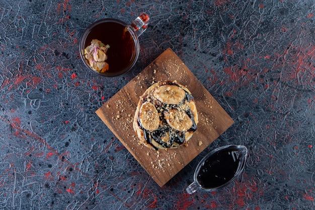 Crêpes avec des tranches de banane et verre de thé chaud sur une surface sombre.
