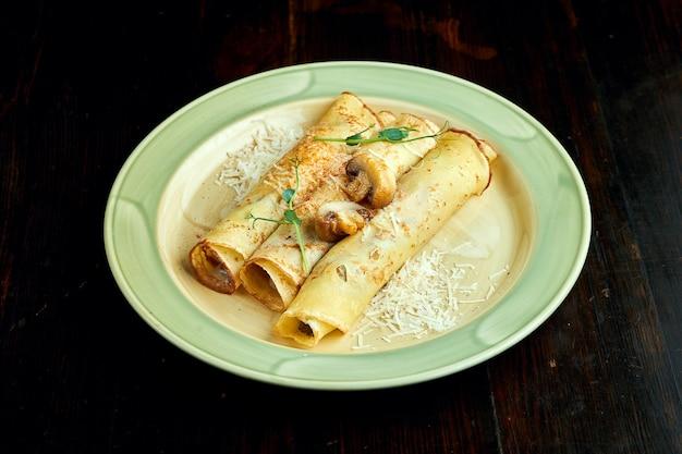 Crêpes ukrainiennes traditionnelles aux champignons servies dans une assiette jaune avec des tomates et de la crème sure sur un fond sombre