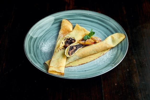 Crêpes ukrainiennes traditionnelles aux graines de pavot servies dans une assiette jaune avec des tomates et de la crème sure sur un fond sombre.
