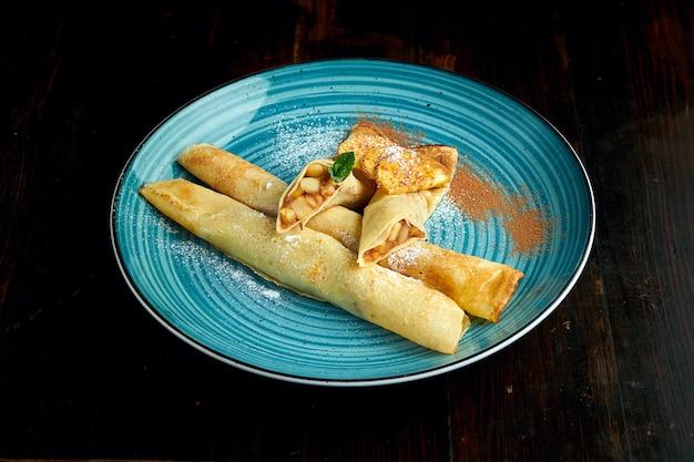 Crêpes ukrainiennes traditionnelles aux pommes servies dans une assiette bleue avec des tomates et de la crème sure sur un fond sombre