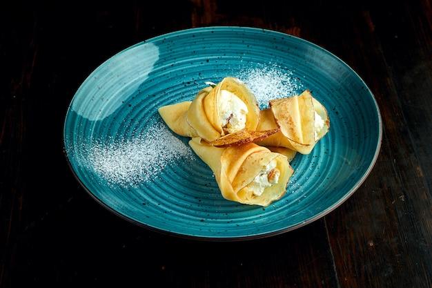 Crêpes ukrainiennes traditionnelles avec du fromage cottage servi dans une assiette bleue avec des tomates et de la crème sure sur un fond sombre.