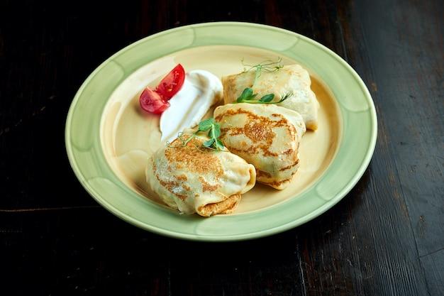 Crêpes ukrainiennes traditionnelles avec jambon et fromage servi dans une assiette jaune avec des tomates et de la crème sure sur un fond sombre.
