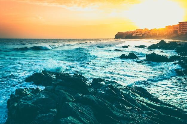 Crépuscule fabuleux derrière la colline d'immeubles au bord de la mer à playa del aguila gran canaria