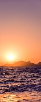 Crépuscule de la nature et concept de vacances à la plage vintage coucher de soleil d'été sur le paysage marin de la côte de la mer méditerranée et vue sur la montagne