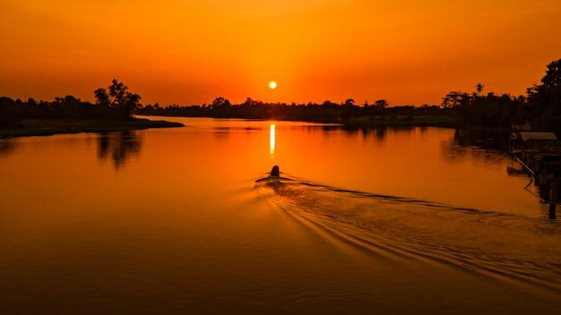 Crépuscule paysage le coucher de soleil se reflétant sur l'eau avec une silhouette de bateau de pêche le soir