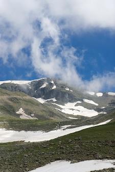 Crête de haute montagne et rochers de neige sous le ciel bleu et les nuages blancs et la brume.