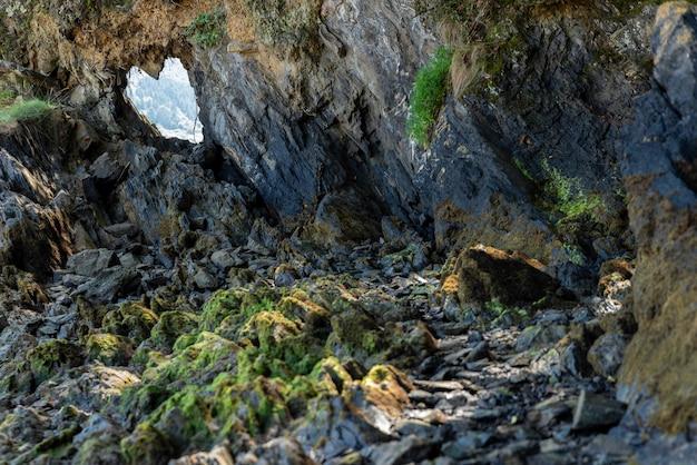 Creux en pierres en forme de coeur avec des pierres et des arbres environnants, horizontalement