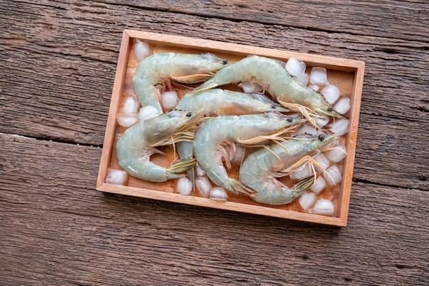 Crevette ou crevette banane fraîche dans une plaque de bois avec de la glace sur fond de table en bois