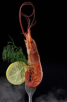 Crevette rouge gros plan sur une fourchette décorée de citron et d'aneth