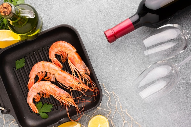 Crevette vue de dessus dans une casserole avec une bouteille de vin