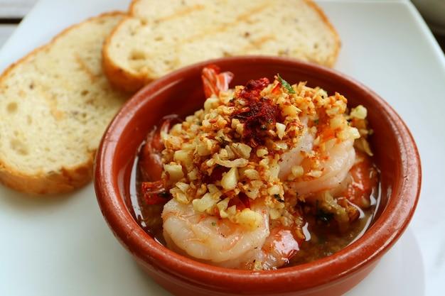 Crevettes à l'ail ou gambas al ajillo, style espagnol, avec tranches de pain tranchées floues en arrière-plan