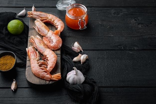 Crevettes argentines rouges crues, sur une planche à découper en bois, sur table en bois noir