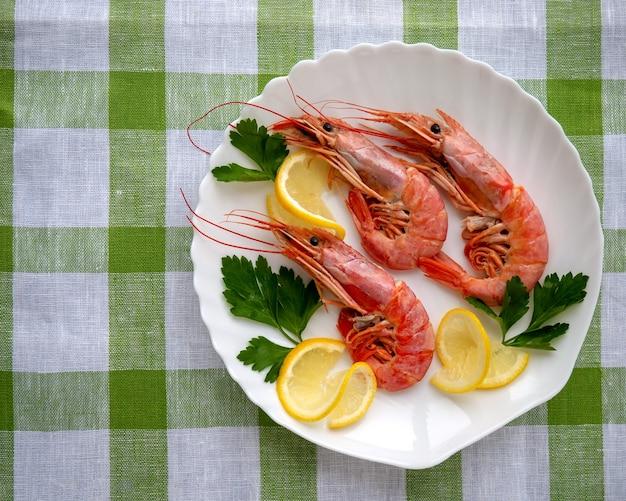 Crevettes sur une assiette blanche avec des feuilles de citron et de persil. sur une table recouverte d'une nappe à carreaux verts et blancs.