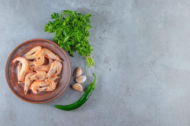Crevettes sur une assiette à côté du bouquet de persil , sur le fond de marbre.