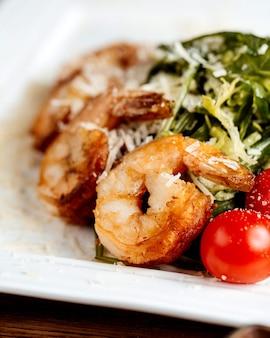 Crevettes aux herbes et tomates saupoudrées de parmesan râpé