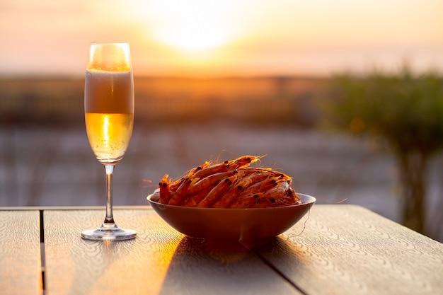 Crevettes à la bière au coucher du soleil près de la mer crevettes d'été au champagne au coucher du soleil concept d'été fruits de mer à la bière coucher de soleil sur la mer avec champagne beau coucher de soleil bière froide aux crevettes crevettes royales