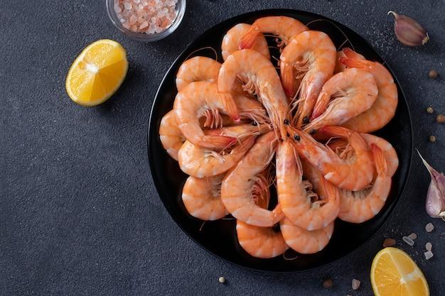 Crevettes bouillies dans une assiette ronde noire et épices sur une surface sombre. vue d'en-haut.