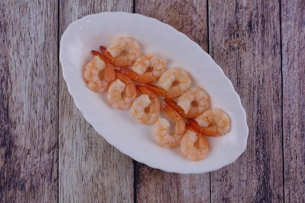 Crevettes bouillies et pelées vue de dessus sur une table en bois usée
