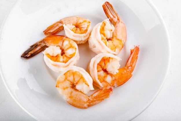 Crevettes bouillies pour ajouter à la pizza sur une plaque blanche
