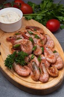 Crevettes bouillies avec sauce à l'ail sur une planche de bois