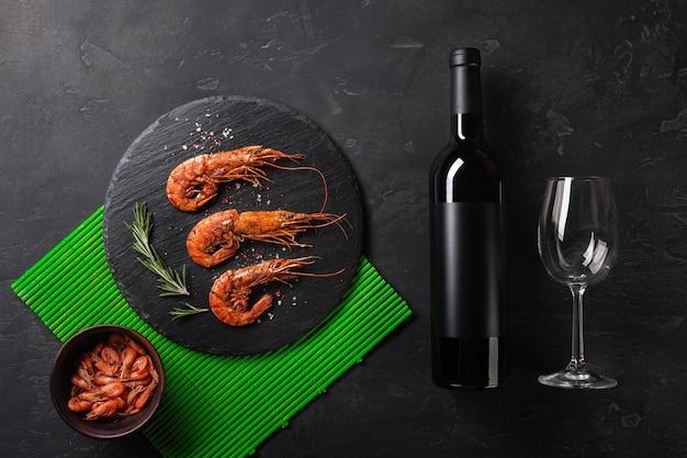 Crevettes avec une bouteille de vin. vue de dessus. espace libre pour votre texte. sur le vieux fond