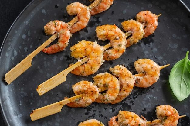 Crevettes en brochette avec épices et herbes servies sur assiette noire. fermer.