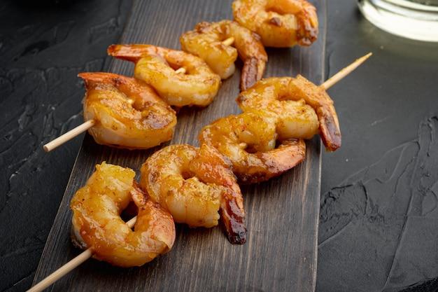 Crevettes en brochettes avec sauce curry chutney à la mangue, sur planche de service en bois, sur fond noir