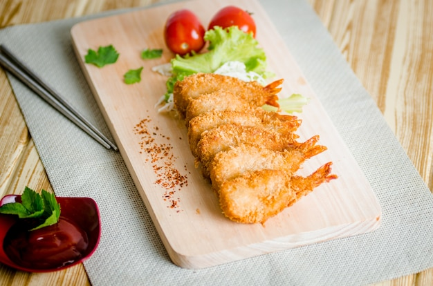 Crevettes butterfly ebi furai servies avec tomate et laitue sur une planche à découper en bois