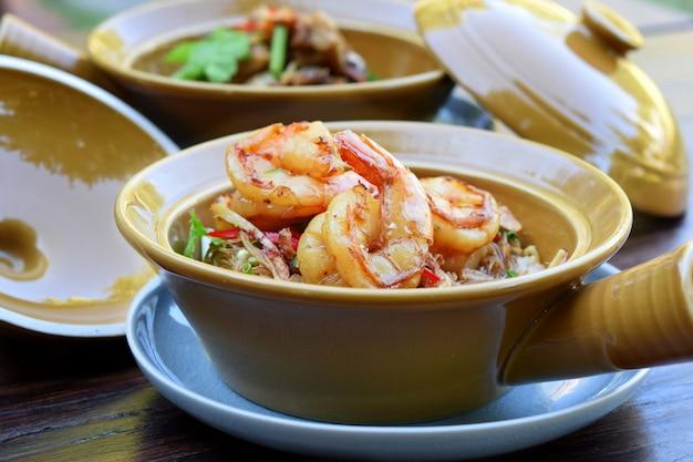 Crevettes en cocotte avec nouilles de verre en pot d'argile sur table en bois