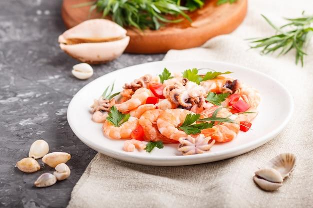Crevettes ou crevettes cuites et petites pieuvres sur une plaque en céramique blanche sur un fond de béton noir et textile en lin. vue de côté, gros plan.