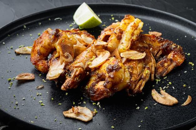 Crevettes ou crevettes à la mangue collantes, sur assiette, sur fond noir