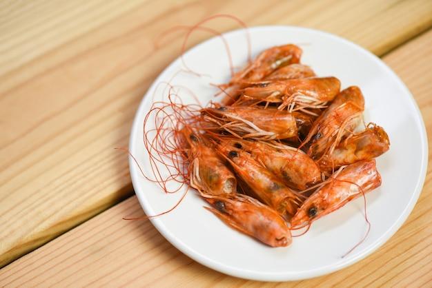 Crevettes croustillantes frites profondes délicieuses épices d'assaisonnement sur plaque et fond de table en bois. crevettes ou crevettes cuites fruits de mer égoïstes