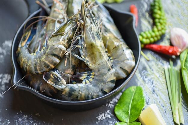 Crevettes crues crevettes sur bol avec herbes et épices pour soupe aigre épicée cuite crevettes tigrées noires fraîches