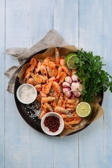 Crevettes crues dans une poêle avec des ingrédients pour la préparation de crevettes frites sur la vue de dessus en bois bleue