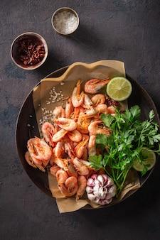 Crevettes crues dans une poêle avec les ingrédients pour la préparation de crevettes frites sur une vue de dessus sombre
