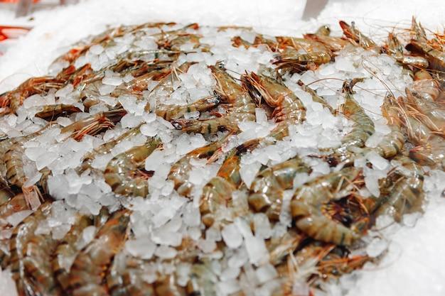 Crevettes crues fraîches close up allongé sur la glace dans un supermarché