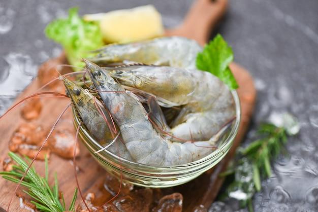 Crevettes crues avec de la glace sur une planche à découper
