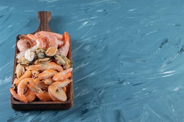 Crevettes crues sur une planche , sur fond de marbre.