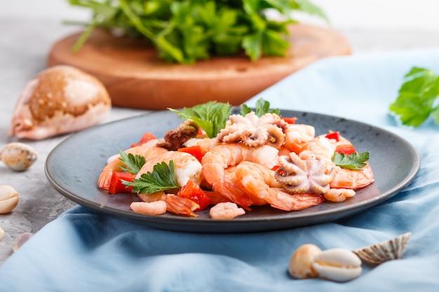 Crevettes cuites ou crevettes et petites pieuvres aux herbes sur une plaque en céramique bleue sur un béton gris. vue latérale, mise au point sélective.