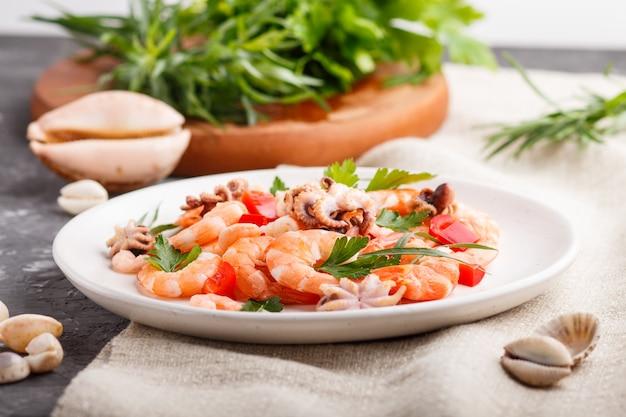 Crevettes cuites ou crevettes et petites pieuvres sur plaque de céramique blanche sur un textile en béton et lin noir. vue latérale, gros plan.