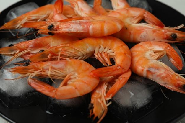 Crevettes cuites savoureuses et glaçons, gros plan