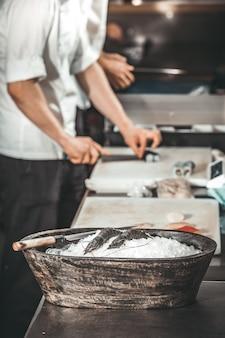 Les crevettes dans le bol. le chef faisant les sushis.