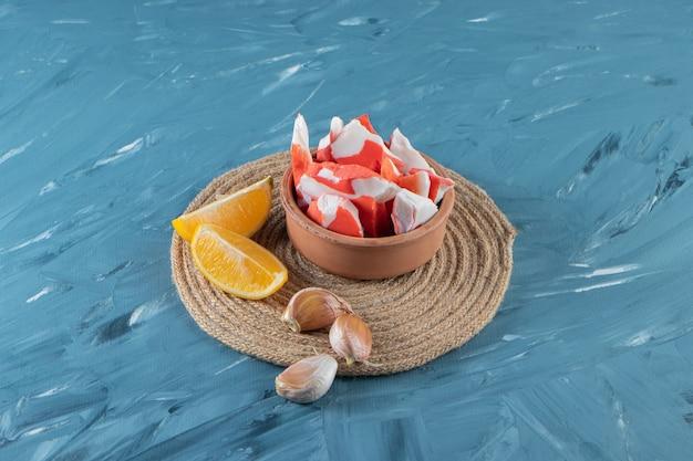 Crevettes dans un bol à côté de citron frais tranché et d'ail sur un dessous de plat, sur la surface en marbre.