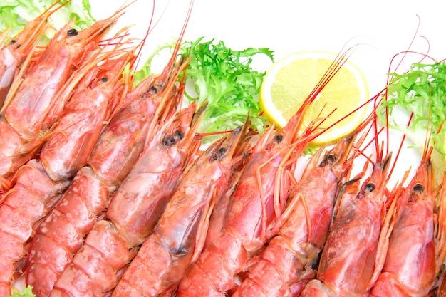 Crevettes fraîches crues avec salade et tranches de citron sur fond blanc