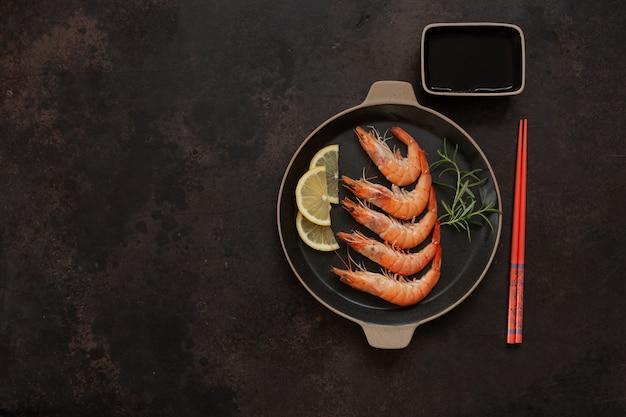 Crevettes fraîches dans un plat noir avec sauce au citron et soja