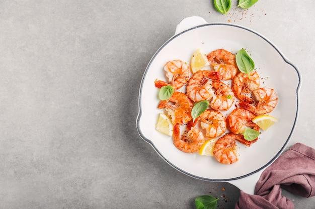 Crevettes fraîches frites aux épices sur une casserole blanche