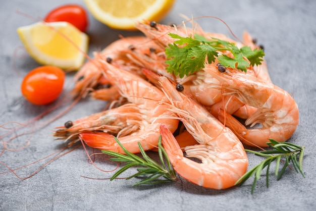 Crevettes fraîches sur une plaque sombre avec des ingrédients herbes et épices - cuisson des crevettes de fruits de mer crevettes servies sur un fond de table