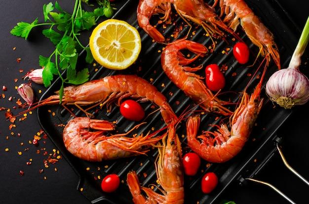 Crevettes fraîches sur une poêle en fer et ingrédients prêts pour la cuisson
