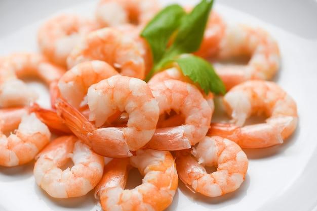Crevettes fraîches servies sur une assiette de crevettes cuites pelées et bouillies